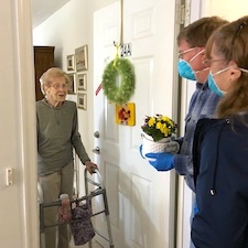 man and woman delivering flowers to elderly woman